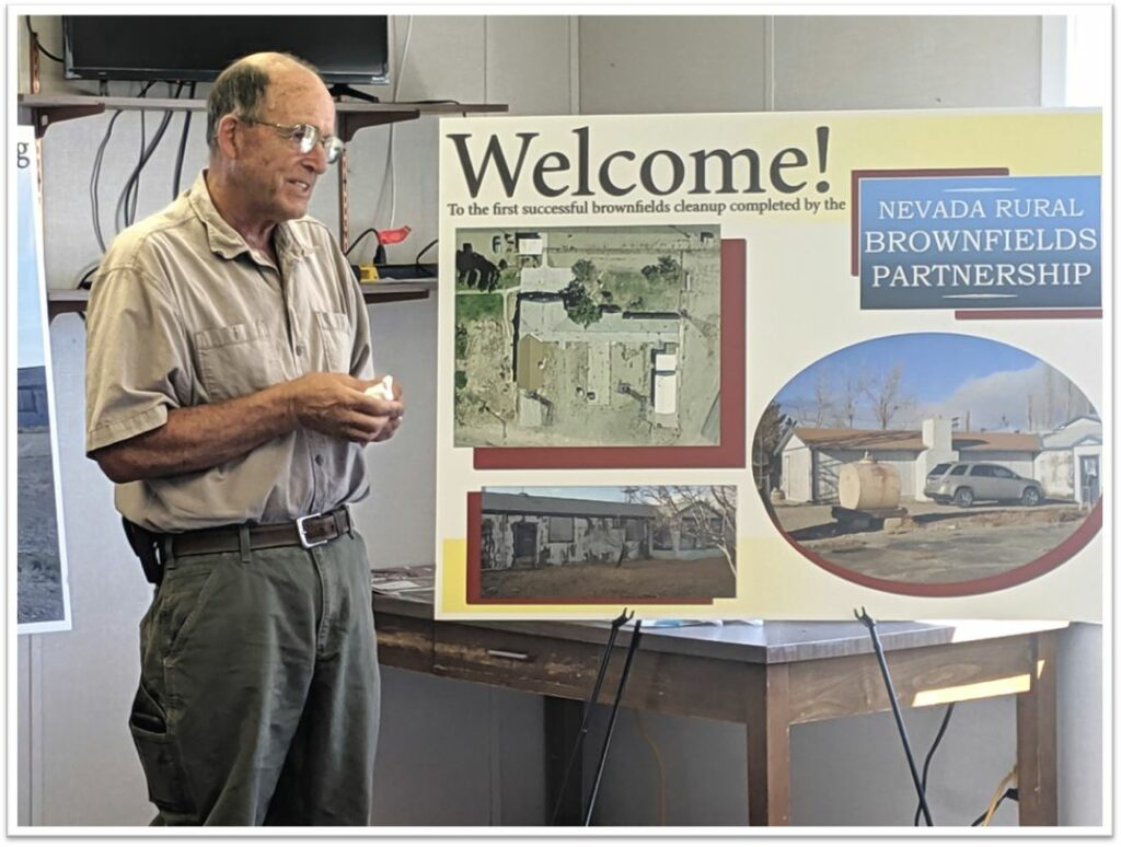 Mark Peterson, FBO Building Operator, stands inside in front of two poster boards welcoming attendees to the first successful brownfields cleanup of the Nevada Rural Brownfields Partnership. He discusses the history of the Tonopah Airport, and the history associated with the Fixed Base Operator Building.